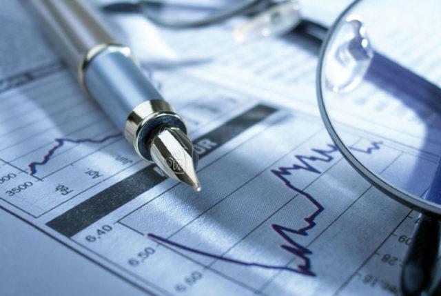 Blatt mit Füller Brille und Wirtschaftsdaten