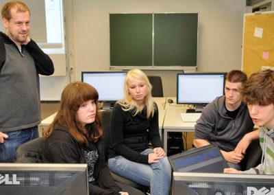 Schülerinnen und Schüler mit Dozent in Computerraum