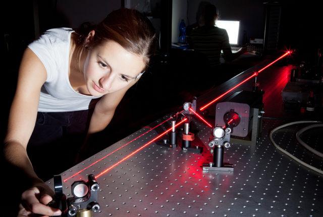 Studentin kalibriert Laser-Versuch
