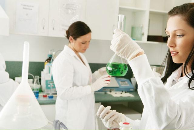 Studierende im Labor mit Erlenmeyerkolben
